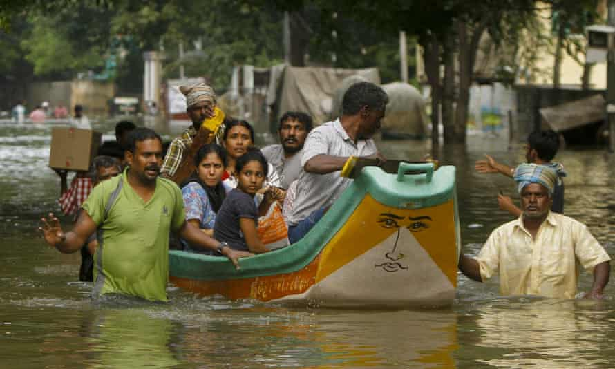 Volunteers help to rescue affected people on a country boat in Chennai.