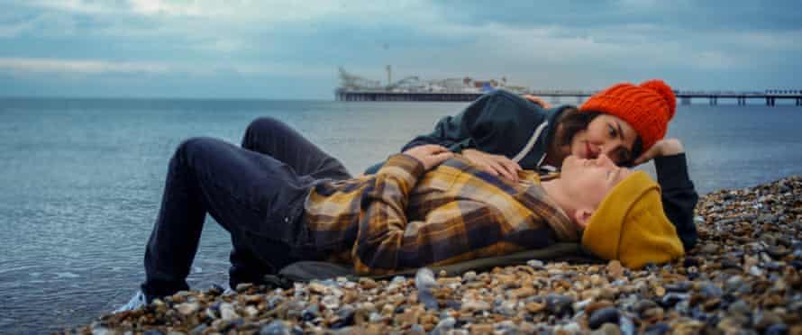 Man and woman lying on a stony beach