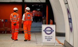 Crossrail employees walk in the new Farringdon underground station of the Elizabeth line which was due to open in December 2018, in London.
