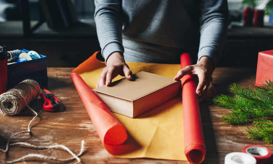 woman wrapping book as christmas giftcropped shot of woman wrapping book in paper as christmas gift