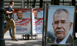 People walk between election posters of Alexander Van der Bellen and Norbert Hofer in Vienna.