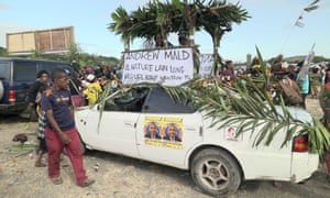 A car is decorated with voting posters at an election rally in the Papua New Guinea capital, Port Moresby.