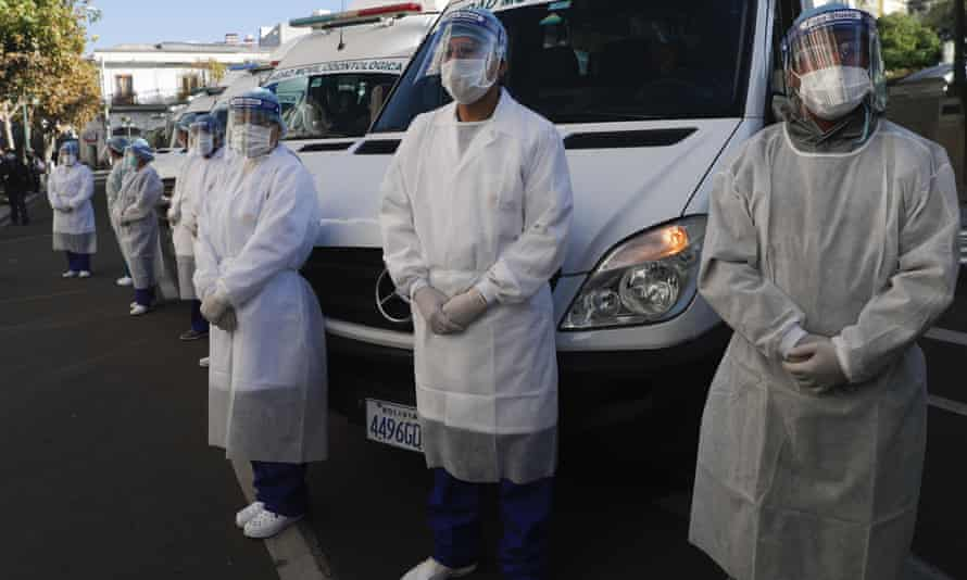 Healthcare workers stand dressed in full protection gear during an inspection in La Paz, Bolivia, on 28 May before departing to the Amazonian region of Beni in a caravan of medical teams to help in the fight against the new coronavirus pandemic.