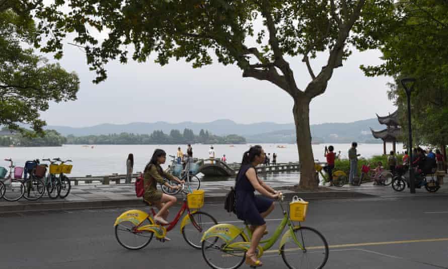 People ride public bike share cycles around Hangzhou's scenic West Lake.