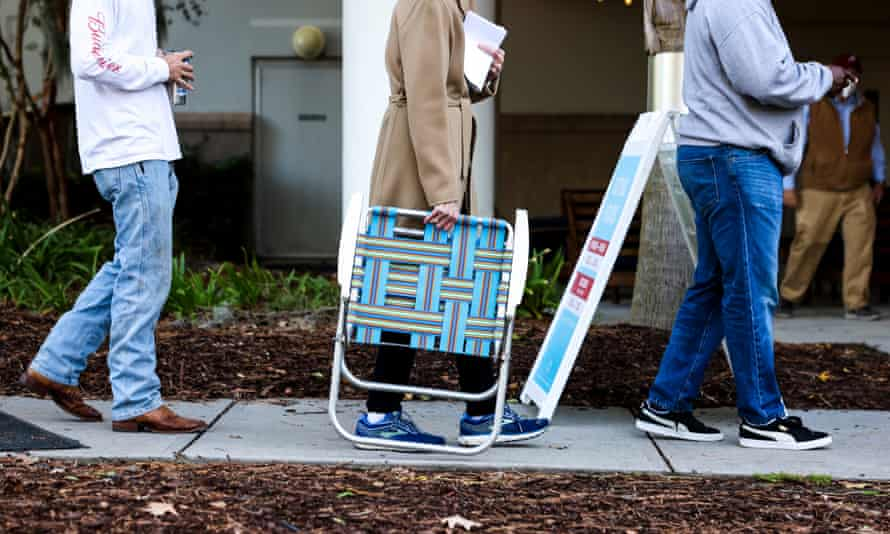A woman carries a chair as she waits in line to vote in Mount Pleasant, South Carolina.