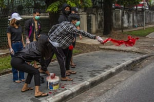 Anti-coup protesters throw red paint on a street during a demonstration in Yangon