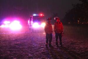 RFS crews fight a fire at the Green Wattle Creek fire near Bargo NSW tonight as it starts to rain. 21st December 2019.