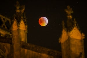 The moon slips into Earth's dark umbral shadow behind the Tours' cathedral in central France
