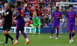 Liverpool goalkeeper Loris Karius looks dejected after fumbling a free kick from Ollie Norburn of Tranmere Rovers leading to a goal .