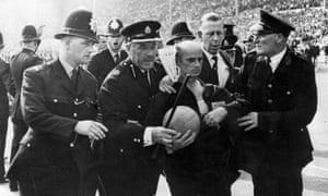 """Save The Ref !Police escort the German referee Rudolf Kreitlein off the Wembely pitch at the end of the England v Argentina quarter-final. """"Not so much a football match as an international incident"""", wrote Hugh McIlvanney in the Observer."""
