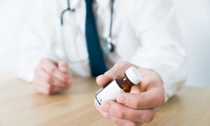 Doctor sitting at desk wearing stethascope handing patient a bottle of medicine