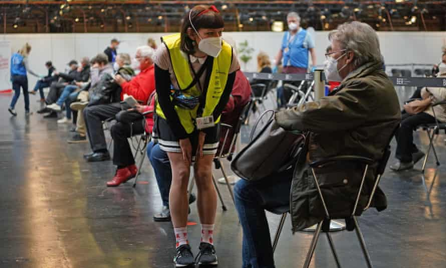 A vaccine centre worker tends to a patient at the Arena Berlin mass vaccination centre in the German capital