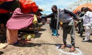 A woman sells fruits to a customer standing in a circle to mark social distance, as a measure to stem the spread of the coronavirus disease at the market centre in Hamarweyne district in Mogadishu, on 16 April.