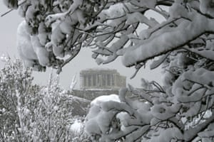 The Parthenon is seen through snow-covered trees.