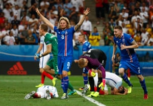 Birkir Bjarnason celebrates as England's Joe Hart and Gary Cahill fall to the ground.