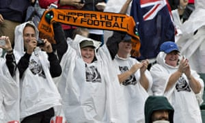New Zealand fans do their best to avoid the rain