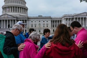 Valerie Vicknair, of Seattle, center in blue, prays for the good of the country on the grounds of the U.S. Capitol as the flag flies at half staff in honor of Supreme Court Justice Ruth Bader Ginsburg on September 25, 2020.