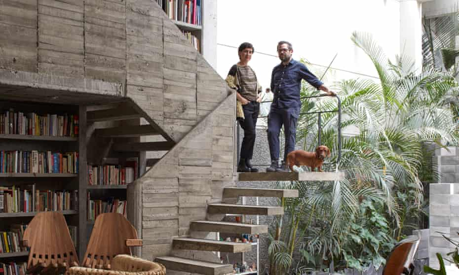 Carla Fernández and Pedro Reyes standing on the concrete stairs in the library.