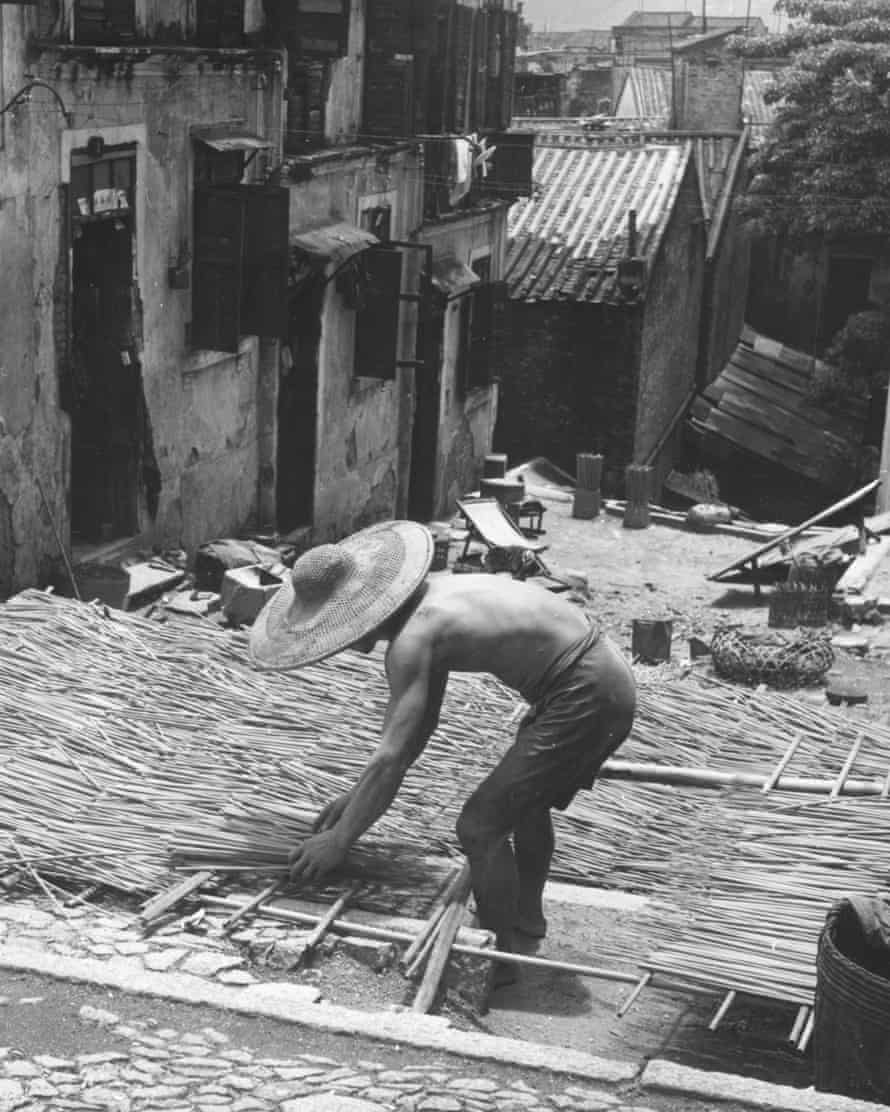 A man lays out incense sticks out to dry in the sun in 1957