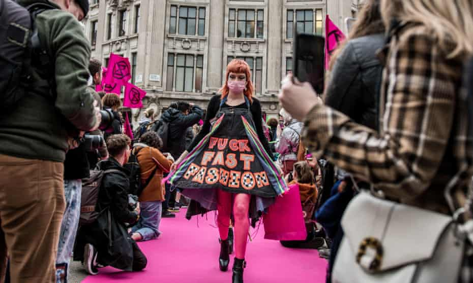 """A young woman in a face mask and a dress that says """"fuck fast fashion"""" parades down a makeshift catwalk on a pink carpet in the city centre, photographed by onlookers on either side."""