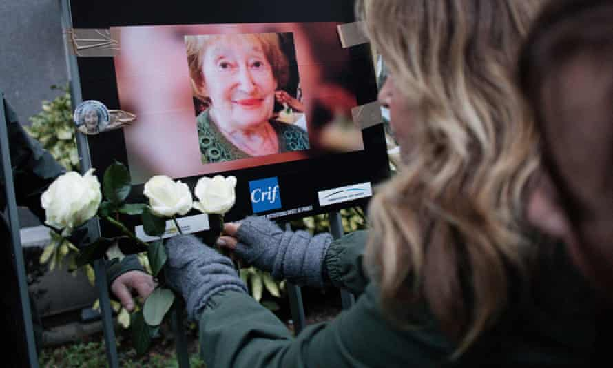 A woman lays flowers by a picture of Mireille Knoll