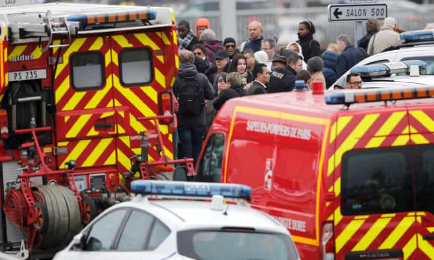 Passengers wait among emergency vehicles at Orly airport.