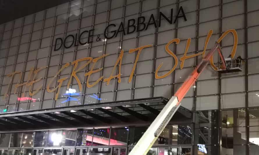 Workers take down the signage for Dolce & Gabbana's Great Show in Shanghai after it was postponed.