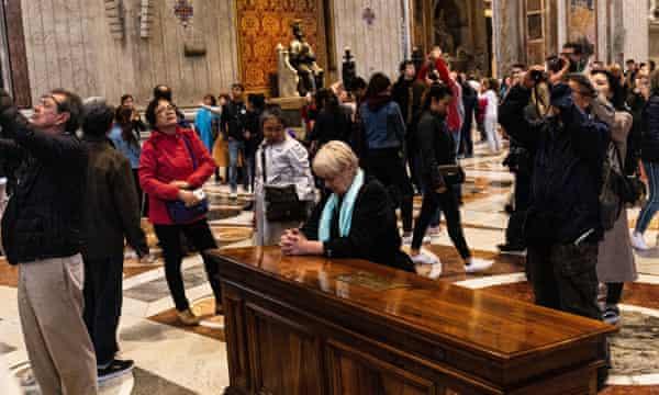 Visitors at the Vatican look up.