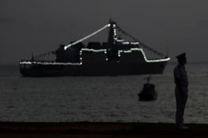 Colombo, Sri Lanka. A naval officer stands guard as a ship is illuminated