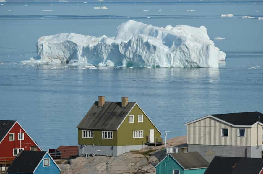 An iceberg floats in Disko Bay behind houses in Ilulissat, Greenland.