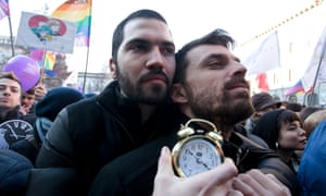 Protesters in Milan hold an alarm clock
