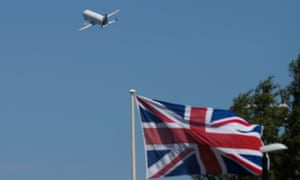 an airbus plane takes off with a union flag in the background