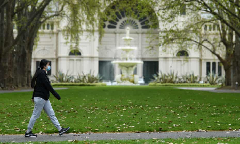 A person wearing a face mask walks through Carlton Gardens in Melbourne