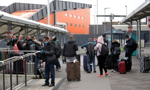 New arrivals queue for a bus at Luton Airport.