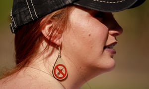 A protester wearing anti-vaccination earrings takes part during the demonstration in Indianapolis