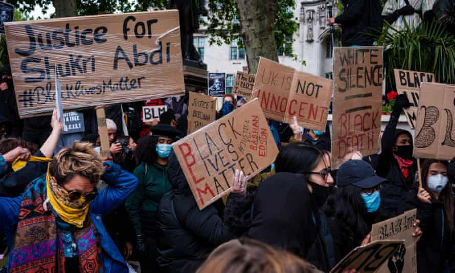 Protestors hold placards during the Black Lives Matter Protest in Parliament Square in London including one calling for justice for Shukri Abdi