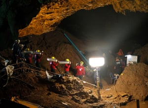 Chiang Rai province, Thailand. Rescuers carry oxygen tanks underground during a rescue operation for 12 missing boys at a cave in Tham Luang Khun Nam Nang Noon Forest Park. The rescuers are attempting to pump water out of the cave complex