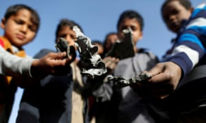 Boys hold missile shrapnel they collected from the site of a Saudi-led air strike in Sanaa, Yemen. Canberra-made weapons are being sold to Saudi Arabia.
