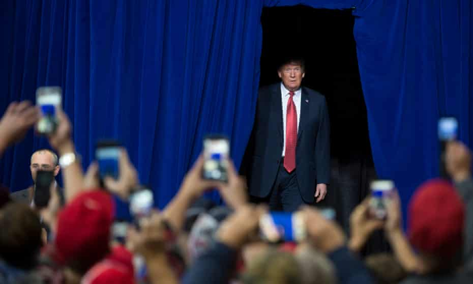 Donald Trump walks out from back stage to cheering supporters in October 2018.