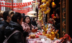 Shoppers purchase Chinese new year-themed gifts from a stall in Chinatown.