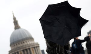 A woman struggles with an umbrella as she walks in front of St Paul's Cathedral in London