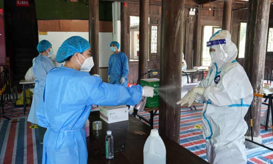 Staff disinfect themselves at a testing site in Nanjing
