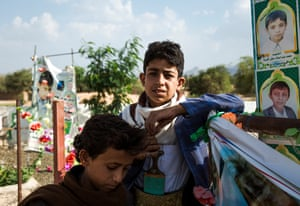 Yusef al-Amir and Mustafa al-Jamal at the village cemetery in Dahyan. Mustafa lives next to the cemetery, and every day visits the graves of his friends who died when an airstrike hit a bus full of schoolchildren.