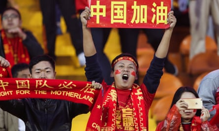 Fans cheer before the match between China and Syria. The Chinese characters read, 'China fighting'