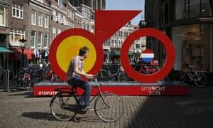 A man rides past the Grand Depart logo for the 2015 Tour de France in Utrecht.