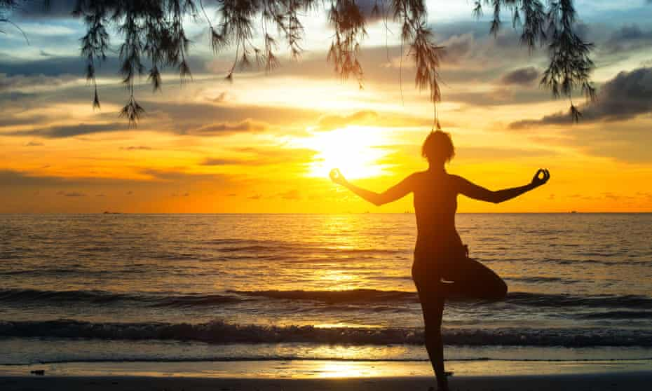 Young woman practicing yoga at sunset on the coast of Ko Chang island, Thailand