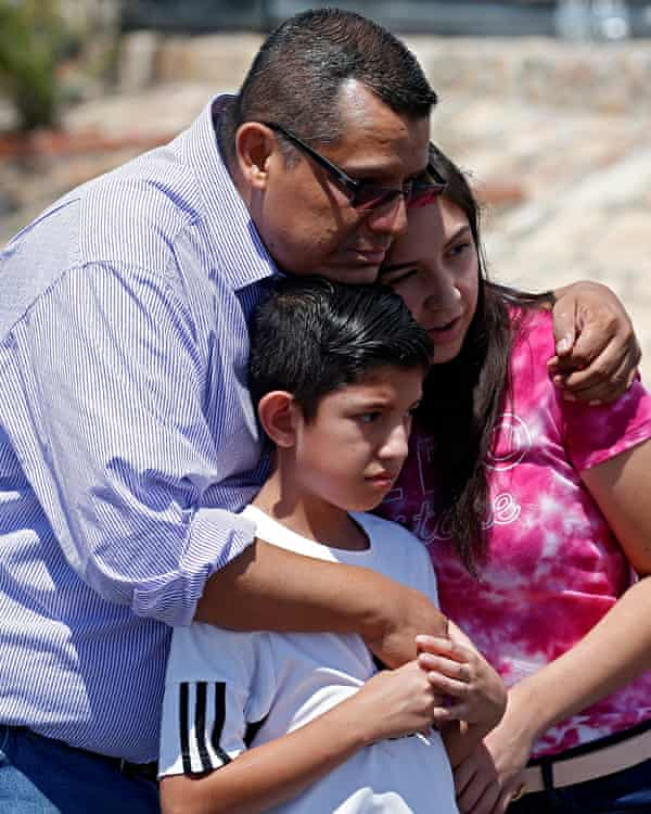 Gilbert Medina comforts his children at a make shift memorial along the street near the scene of a mass shooting at a Walmart in El Paso, Texas.