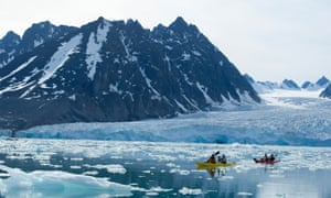 Kayakers at Monaco glacier, Svalbard, in the Arctic.