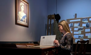 A lady sits at a recreation of an investigators desk into the Cambridge Spies
