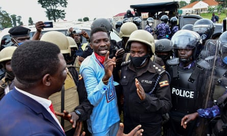 Ugandan presidential candidate Bobi Wine i is led into a vehicle by riot policemen in Luuka district on 18 November 2020.